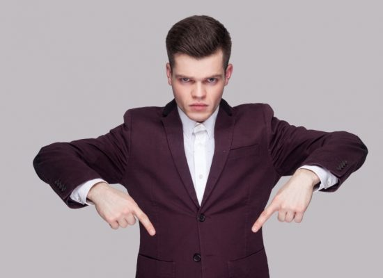 Here and right now. Portrait of serious handsome young man in violet suit, white shirt, standing, looking at camera and pointing down with raised arms. indoor studio shot, isolated on grey background.